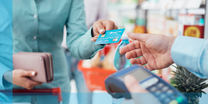 Woman at check out register using credit card.