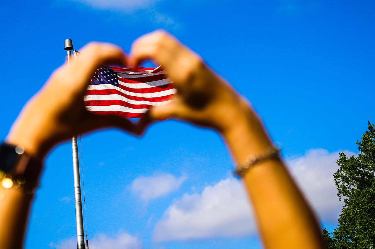 Heart hands around flag